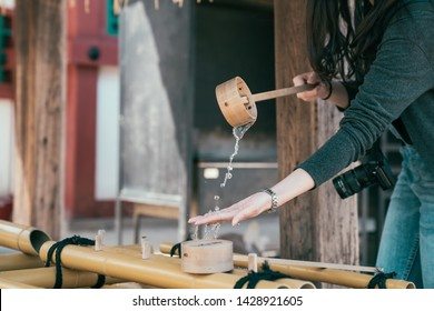 woman travel photographer visit in tennoji osaka japan. girl tourist washing hands in japanese purification fountain in shinto before praying in temple. traveler using bamboo stick with water