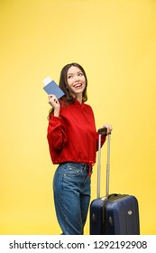 Woman travel. Young beautiful asian woman traveler with suitcase and passport on yellow background