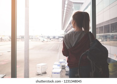 Woman traveler with backpack in airport departure gate. Add vintage tone.