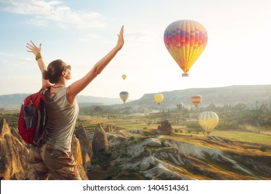 Woman traveler with backpack enjoying the hot air balloons at the hill of Goreme, Cappadocia, Turkey.