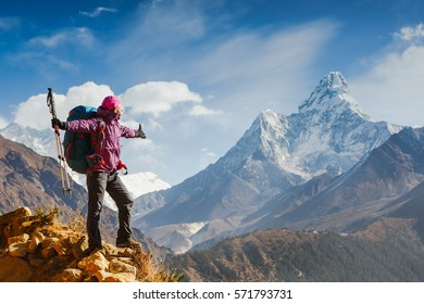 Woman Traveler with Backpack enjoying the mountains in Himalayas. Everest base camb trek