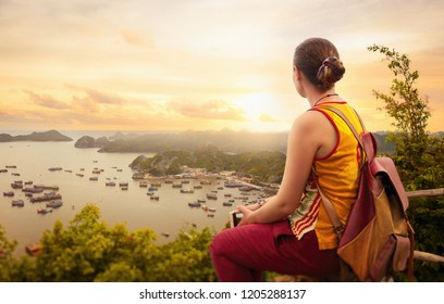 Woman traveler with backpack, enjoying view coast of the bay of Cat Ba at sunset. Vietnam