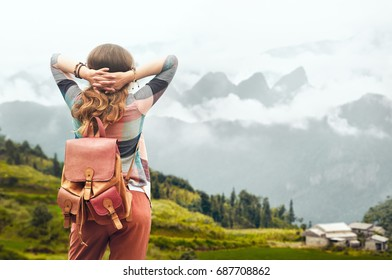 Woman traveler with backpack enjoying view at mountains in fog. 