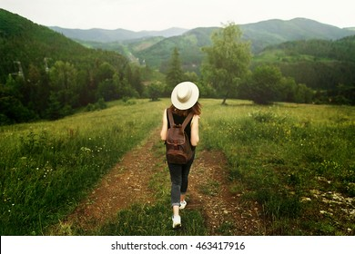 woman traveler with backpack and  hat walking in amazing mountains and forest, wanderlust travel concept, space for text, atmospheric moment. earth day