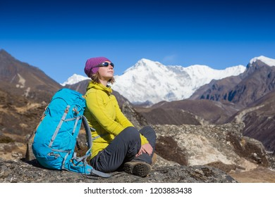Woman Traveler with Backpack hiking in Mountains with beautiful summer Himalayas landscape on background