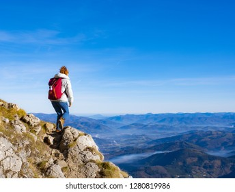 Woman Traveler with Backpack hiking in the Mountains. mountaineering sport lifestyle concept.
