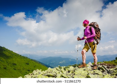 Woman Traveler with Backpack hiking in the Mountains