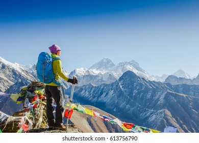 Woman Traveler with Backpack hiking in Mountains with beautiful Himalaya landscape on background. Mountaineering sport lifestyle concept