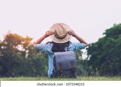 Woman traveler with backpack holding hat and looking at the view in forest, travel concept