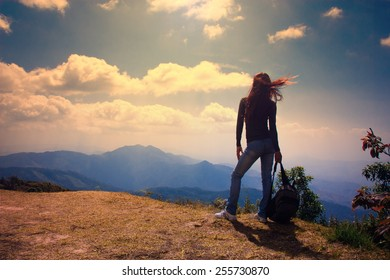 Woman Traveler with Backpack looking at mountain landscape on sky background