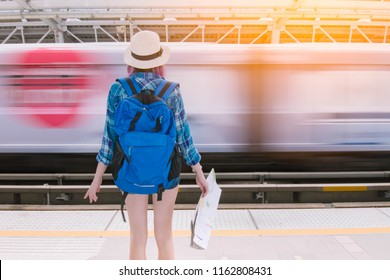 Woman traveler backpacker waiting the sky train at skytrain station,Travel concept.