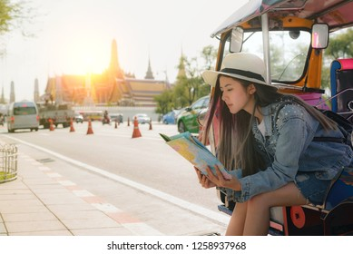 "woman traveler with bag cross body and hat by ""tuk tuk"" look at the temple ""wat phra kaew"" and background from Bangkok Thailand. Traveling Thailand."