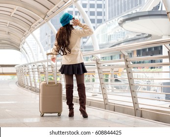 Woman traveler with bag, luggage, suitcase arrival at the airport during traveling, travel, trip for woman concept, say hi, good bye to friend.