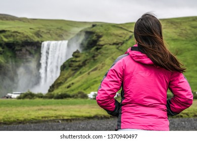 Woman traveler at beautiful scenery of the majestic Skogafoss Waterfall in countryside of Iceland in summer. Skogafoss is the top famous natural landmark and tourist attraction of Iceland and Europe.