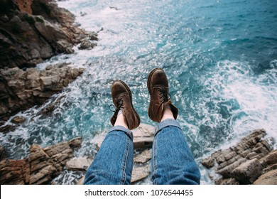 Woman traveler in blue denim jeans and chunky brown leather boots for hiking adventures sits on edge of cliff or rock over ocean water, inspiration for travel blog and summer nomad blog lifestyle
