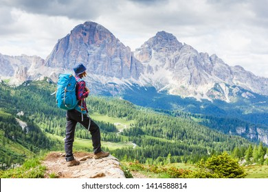 Woman traveler with breathtaking landscape of Dolomites Mounatains in summer, Italy. Travel Lifestyle wanderlust adventure concept