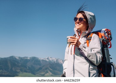 Woman traveler drinks tea on the mountain top