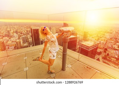 Woman traveler enjoying at binocular from Oue Skyspace Bank Tower in Los Angeles, California, United States at sunset light. Happy tourist at panoramic terrace above Downtown of LA skyline.