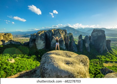 Woman traveler enjoying spectacular Meteora landscape in Thessaly, Greece. Happy female hiker freedom with arms raised outdoors. Panoramic view from best view point Psaropetra. Tourism in Europe.