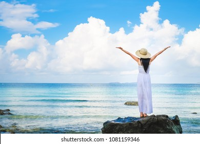 woman traveler enjoying for view of the beautiful sea on her holiday. Lady tourist standing on the rock and rise her hand on the beach.