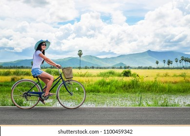 woman traveler enjoying for  view of rice field. Asian lady tourist riding a bicycle and looking for view of nature on holiday.