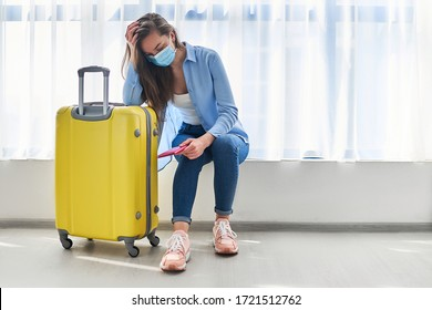 Woman traveler in face protective mask with suitcase affected by flight delay and cancelled travel and vacation. Travel ban during coronavirus outbreak and covid-19 ncov virus epidemic
