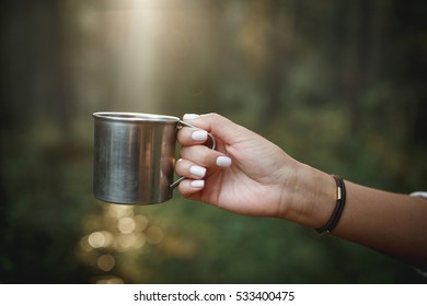 Woman traveler hands holding cup of tea the outdoors. Adventure, travel, tourism and camping concept. Hiker drinking tea from mug at camp