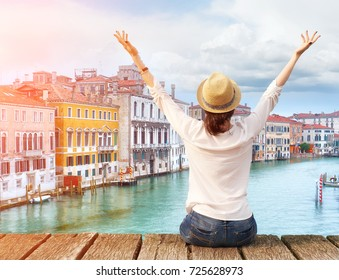 Woman traveler in hat with arms raised on bridge in Venice. Back view with copy space