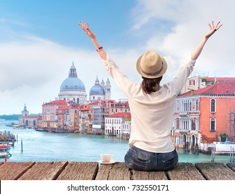 Woman traveler in hat with arms raised and cup of coffee on bridge in Venice