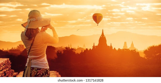 Woman traveler in hat enjoying sunset views of Buddhist stupas in the ancient Bagan. Myanmar, Asia. 