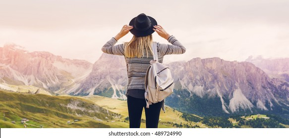 Woman traveler hipster  with backpack holding hat and looking forward  at amazing mountains and valley view. Space for text. Wearing stylish boho fall outfit.