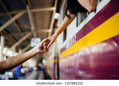 Woman traveler hold her boyfriend hands from  train to say goodbye at Hua Lamphong station at Bangkok train station, Thailand. travel concept,fillter color effect.