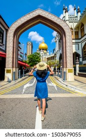 Woman traveler holding hat and looking at The Masjid Sultan mosque located in Kampong Glam in Singapore city.