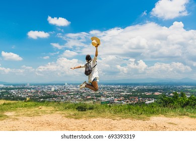 Woman traveler jumping on hill top her arms open felling freedom with blue sky and cityscape background, Hatyai viewpoint, Travel in Thailand
