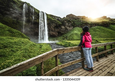 Woman traveler at Magical Seljalandsfoss Waterfall in Iceland located near ring road of South Iceland. Majestic and picturesque, it is one of most photographed breathtaking place of Iceland wilderness