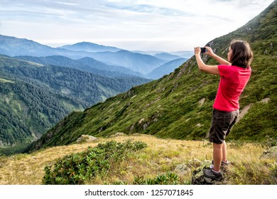 The woman - a traveler makes mountains pictures on a smartphone, a beautiful summer day.