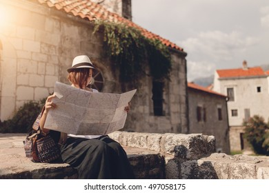 Woman traveler with map in old town at daytime