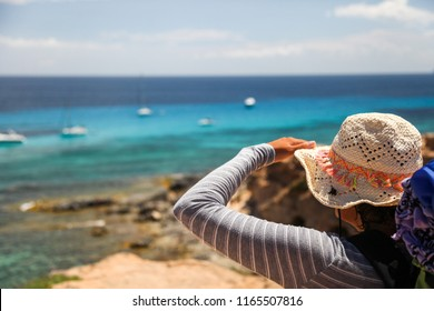 Woman traveler observes a coastal landscape from the top of a cliff