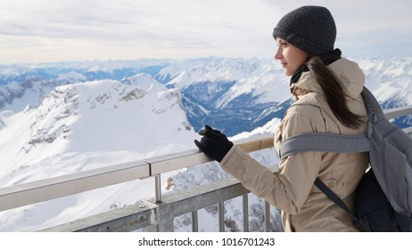 Woman traveler on the top of Zugspitze. It is the highest peak of Wetterstein mountains in Germany.  It lies south of the town of Garmisch-Partenkirchen. Alps.