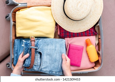 Woman traveler packing clothes in a suitcase for a new journey. Luggage for travel holidays and vacation. Top view