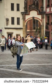 Woman traveler with a paper map on a square of European city