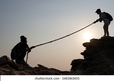 A woman traveler pulls hands her friend up from below with rope. Ideas for success, teamwork and leadership concept .