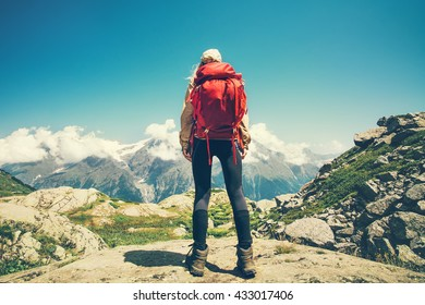Woman Traveler with red backpack mountains and clouds landscape on background Travel Lifestyle concept adventure summer vacations