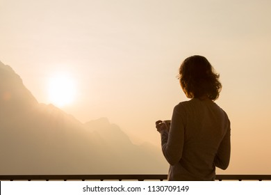 Woman traveler silhouette starting new day enjoying morning coffee looking at peaceful serene sunrise on morning sky watching sunlight above mountains landscape relaxing on travel vacation, rear view
