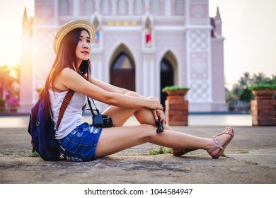 woman traveler sitting in front of the church.tourist young lady have a good time on vacation. beautiful Asia woman go to travel on holiday.