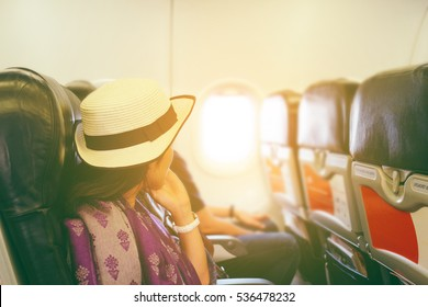 Woman traveler sitting on aircraft and seeing at window