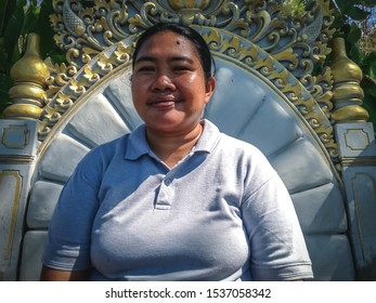 Woman Traveler Sitting On Carved Seat Of The Throne In The Tropical Garden Park At Tangguwisia Village, North Bali, Indonesia