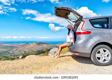 Woman traveler sitting on hatchback car with mountain background.