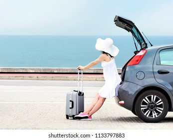 Woman traveler sitting on hatchback car