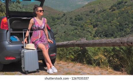 Woman traveler sitting on hatchback car outdoor. Summer vacation and traveling